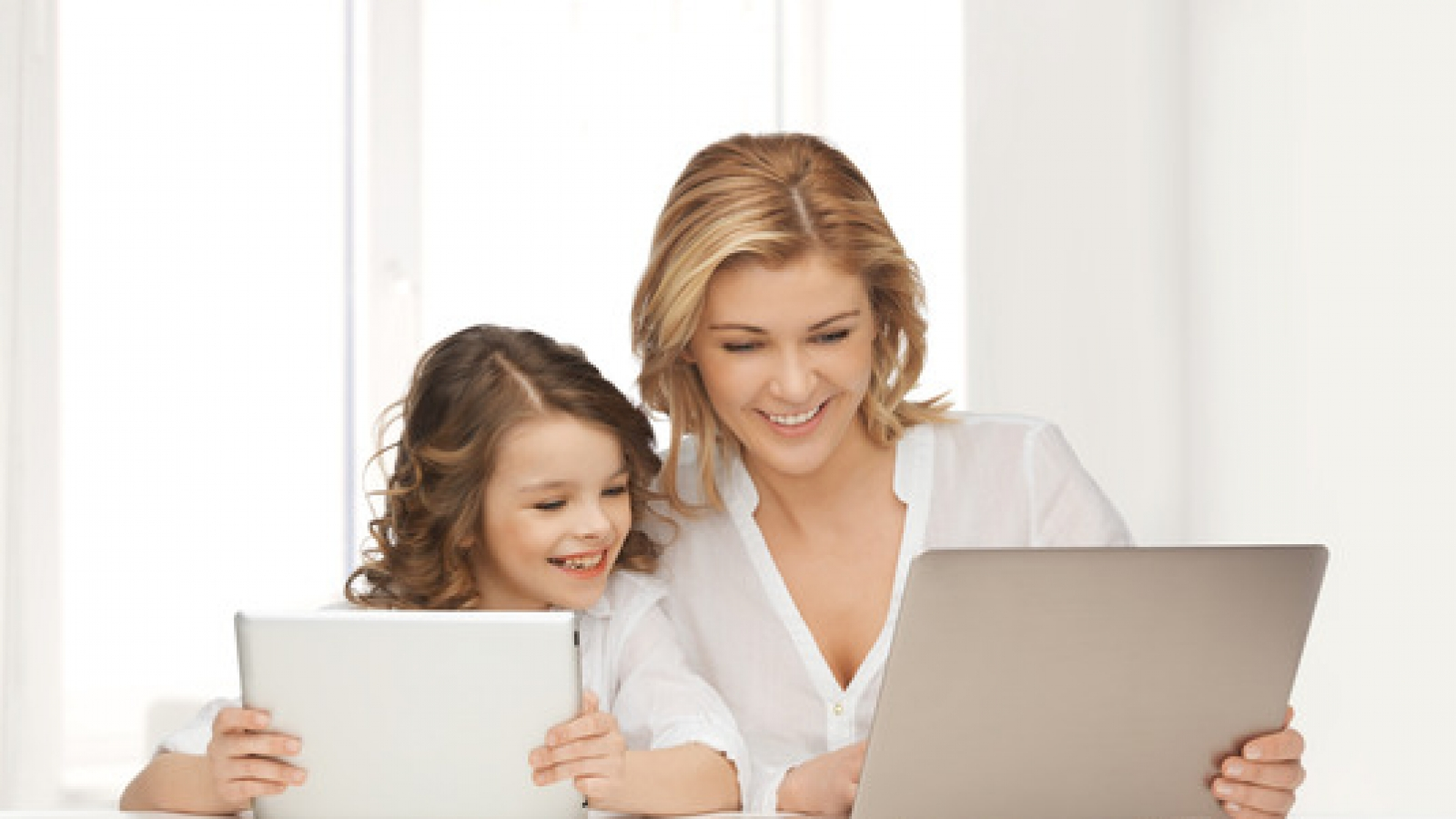 mother with girl looking to laptop and tablet pc